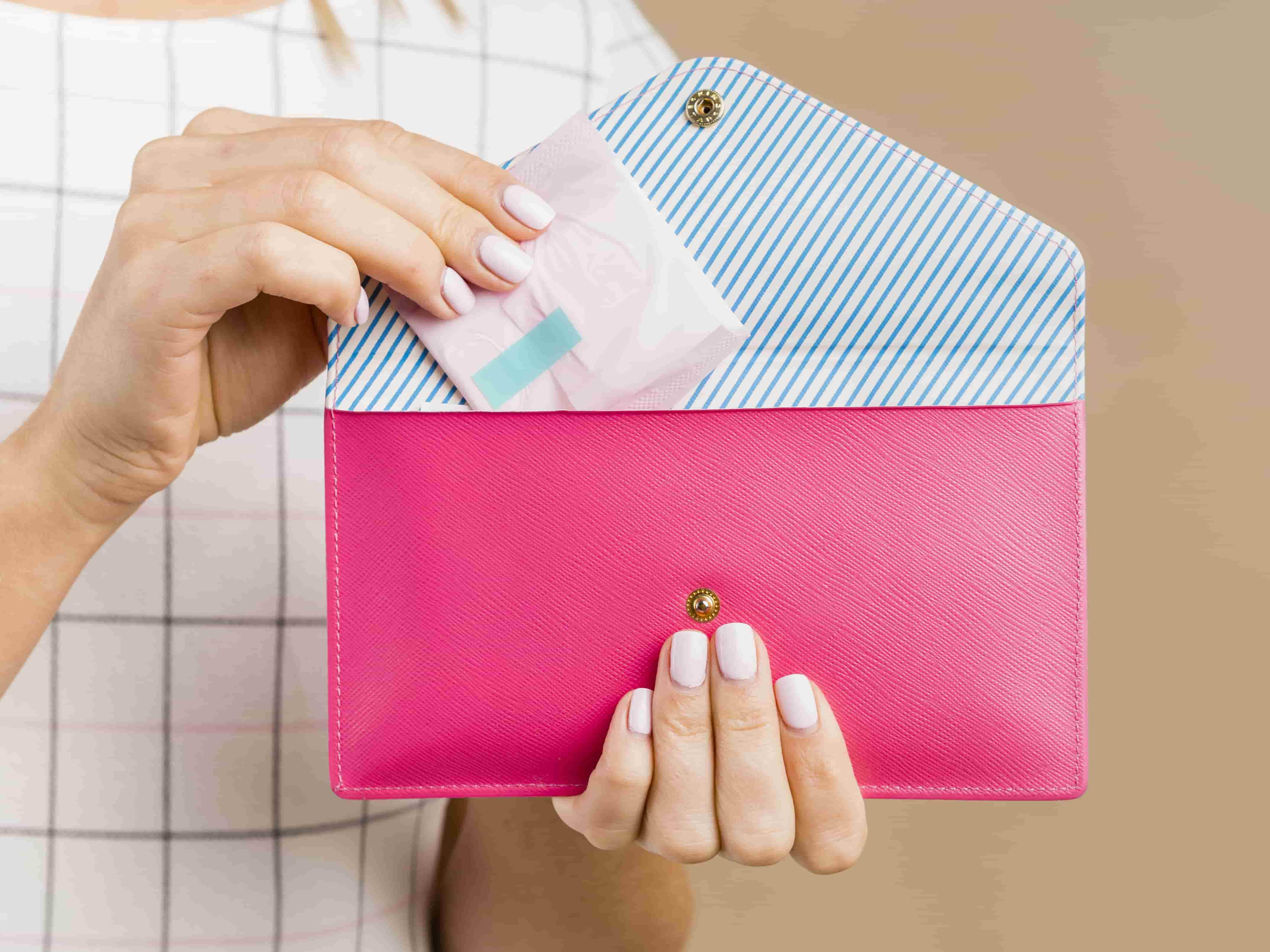 femme qui sort une serviette hygiénique de son portefeuille
