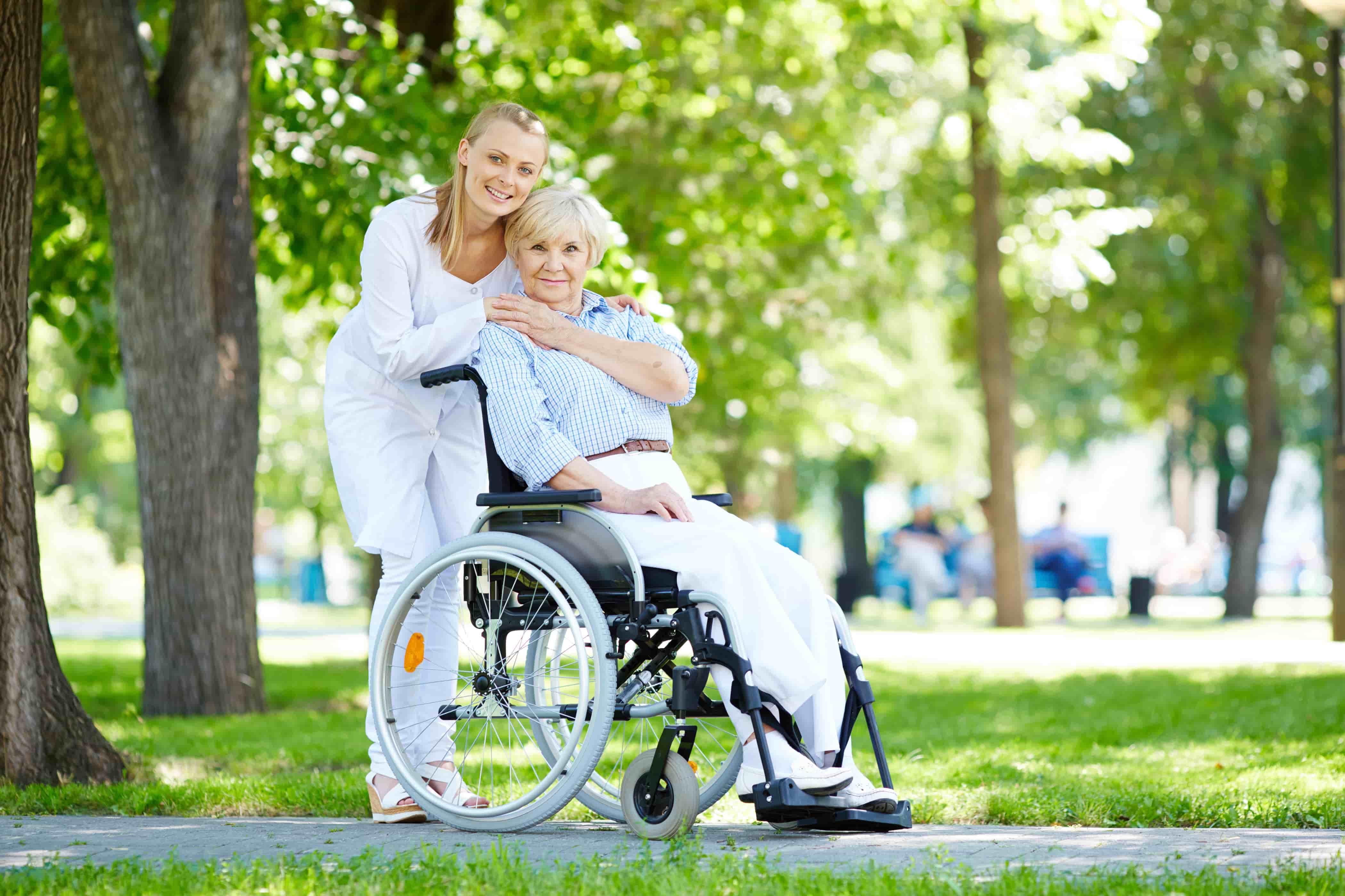 infirmière avec une personne âgée dans un fauteuil roulant