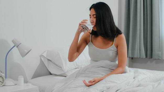 femme buvant de l'eau dans son lit pendant une insomnie